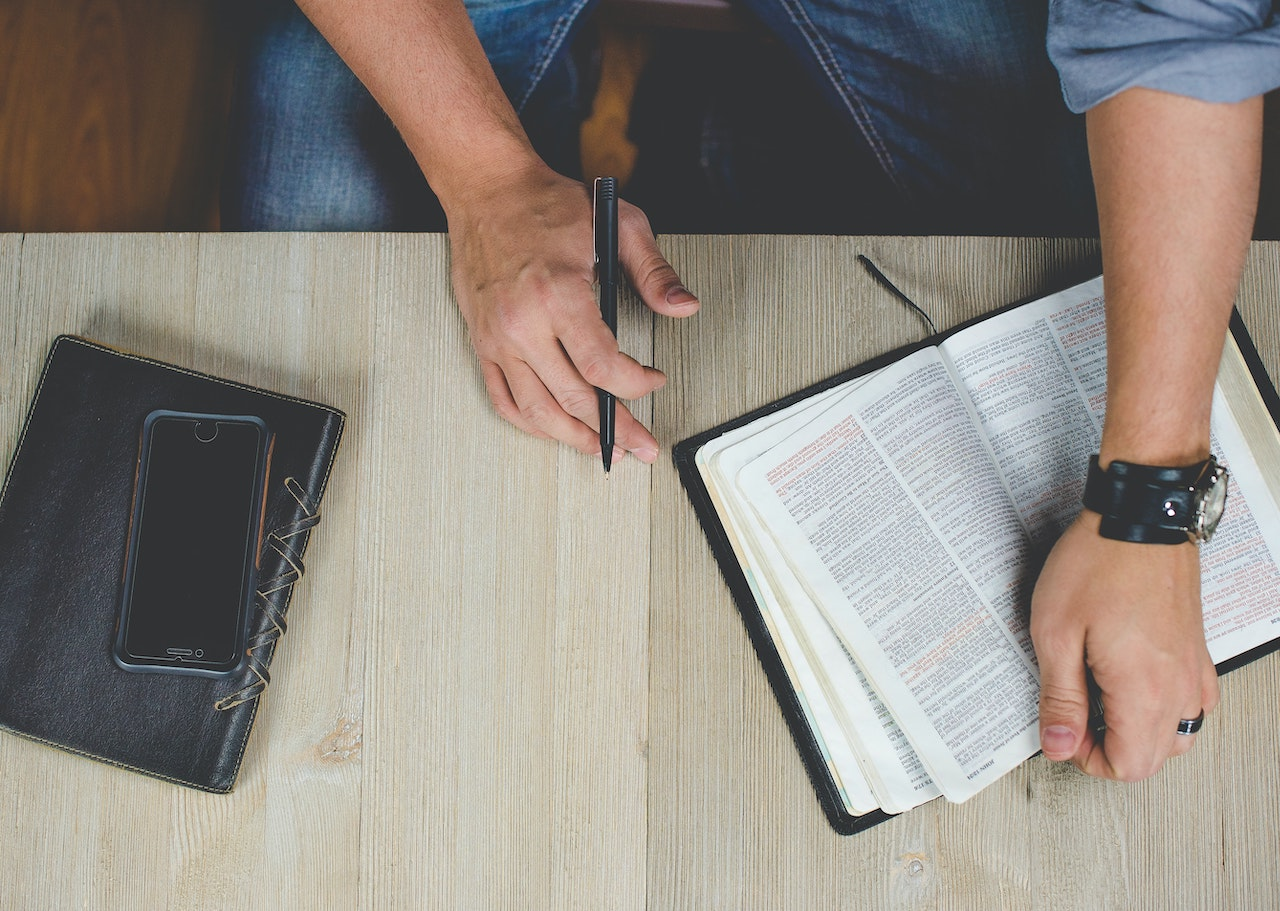 Man working with a mobile phone and a bible